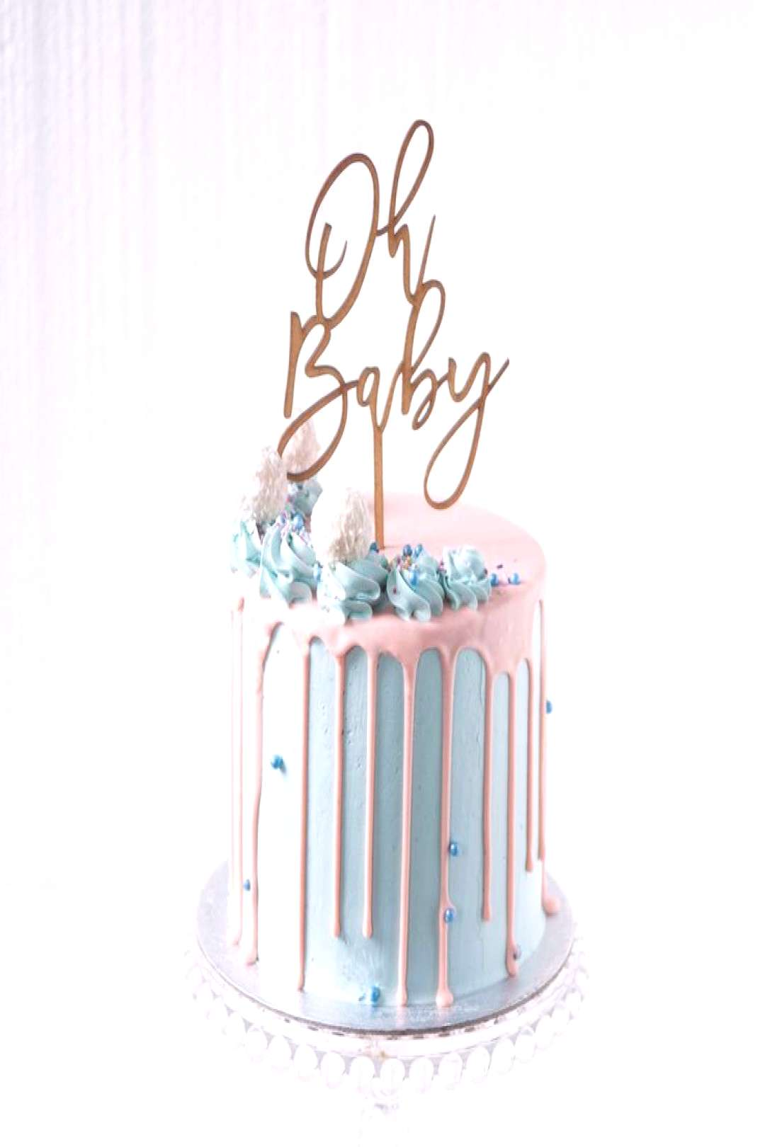 A stunning gender reveal drip cake, complete with contrasting baby blues and blush pinks. Adorned w